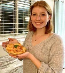 Ava holding a dish of feta pasta