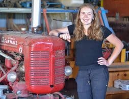 Girl stands beside Farmall Super A tractor