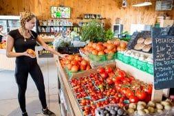 Cashier checks tomato display at Lee and Maria's